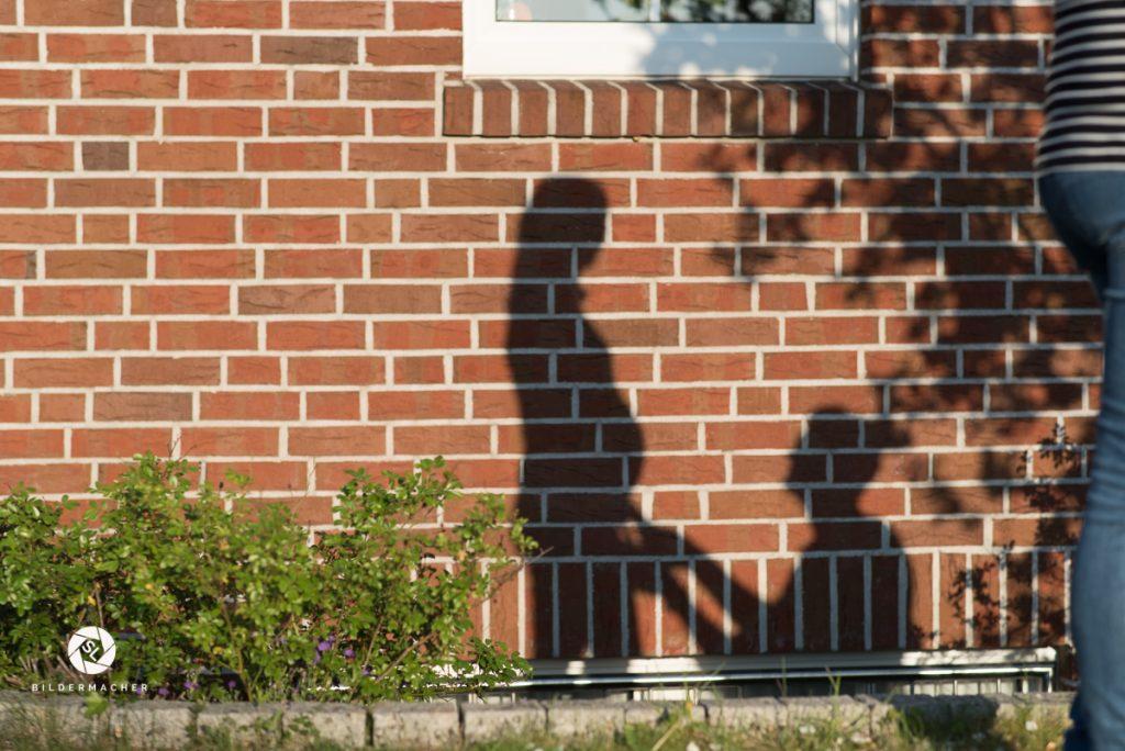 Schatten eines Mannes der vor seiner schwangeren Frau kniet
