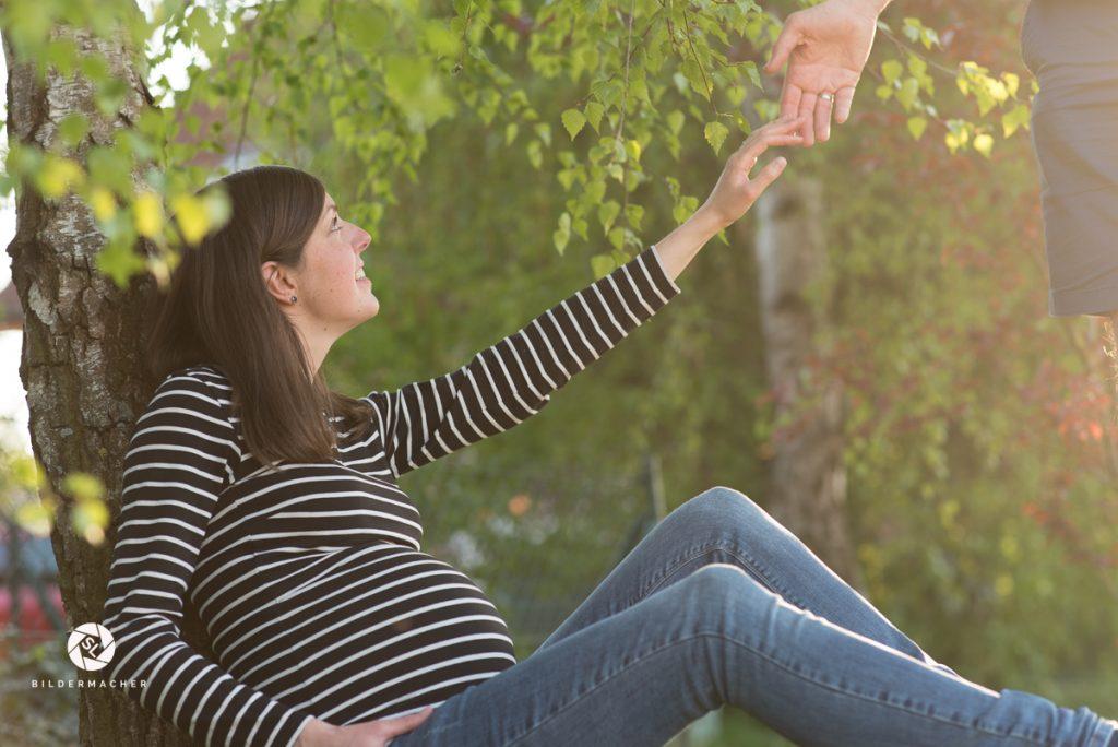 Schwangere Frau sitzt unter einem Baum und reicht ihrem Mann die Hand