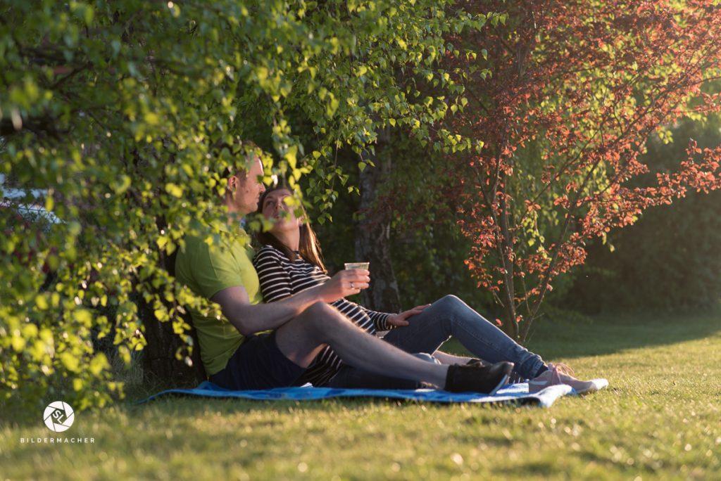 Paar sitzt mit Glas unter einem Baum